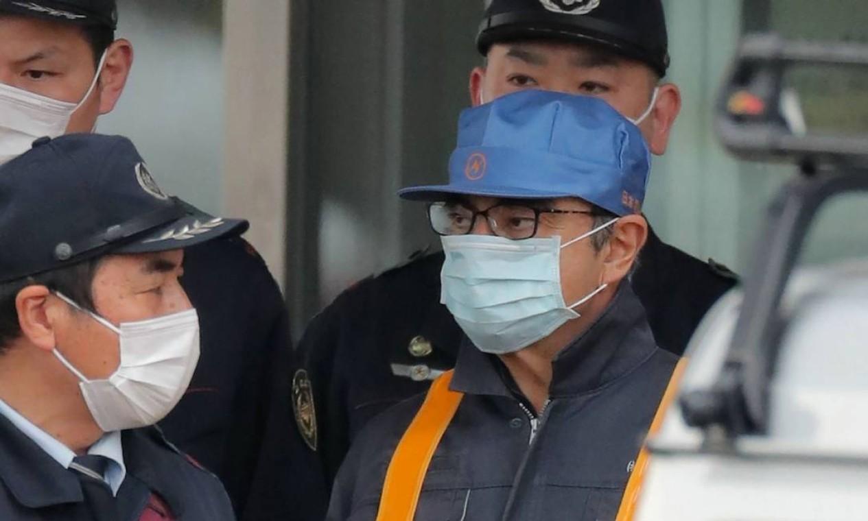 O ex-presidente do Conselho de Administração da Nissan, Carlos Ghosn (de boné azul claro) é escoltado enquanto sai da Casa de Detenção de Tóquio, em abril de 2019. Ele foi preso pela primeira vez em Tóquio em novembro de 2018. Foto: JIJI PRESS / AFP