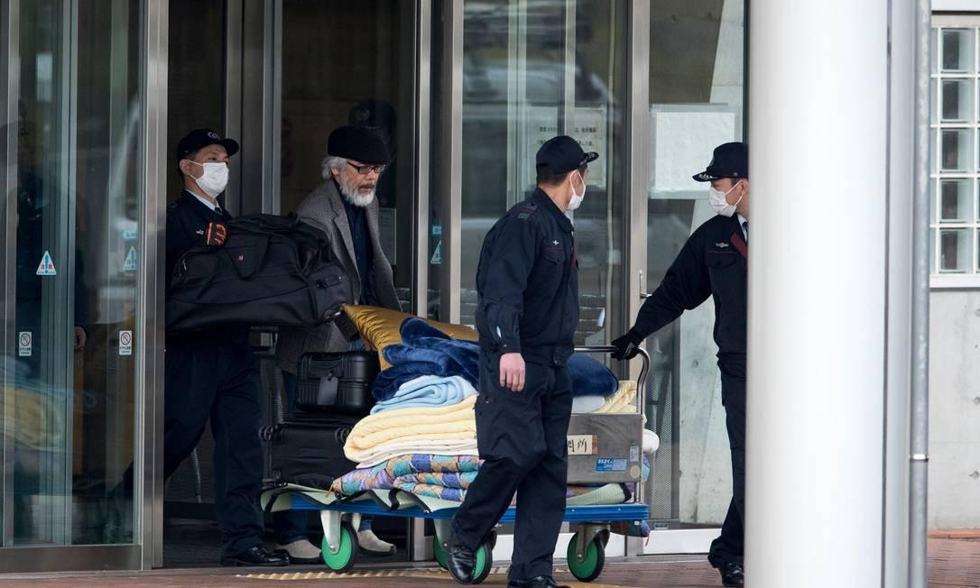 Takashi Takano (de boina preta), um dos advogados de Carlos Ghosn, e seguranças transportam bens pessoais antes da liberação do ex-executivo da Nissan Foto: BEHROUZ MEHRI / AFP