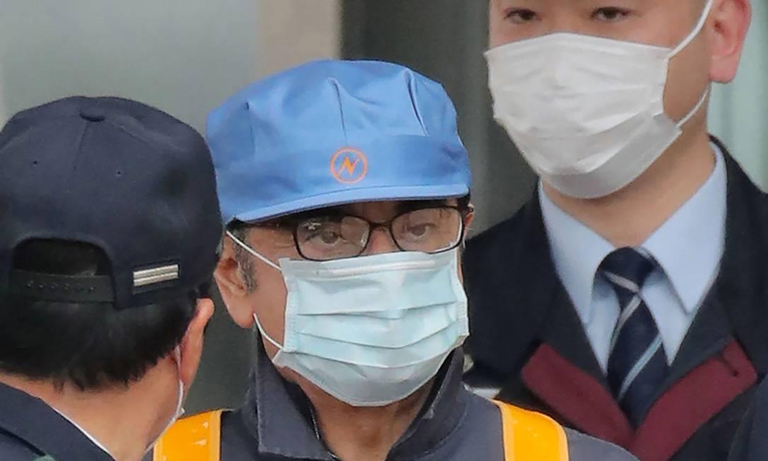 De boné azul e máscara cirúrgica, Ghosn deixa a prisão. Ele é acusado de fraude fiscal Foto: JIJI PRESS / AFP