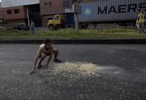 Jovem coleta grãos que caminhou deixou cair sobre o asfalto em Puerto Cabello, na Venezuela Foto: Fernando Llano / AP/23-01-2019