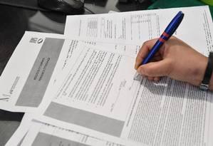 Italiana preenche ficha para se inscrever na Renda Cidadã, espécie de Bolsa Família na Itália Foto: TIZIANA FABI / AFP