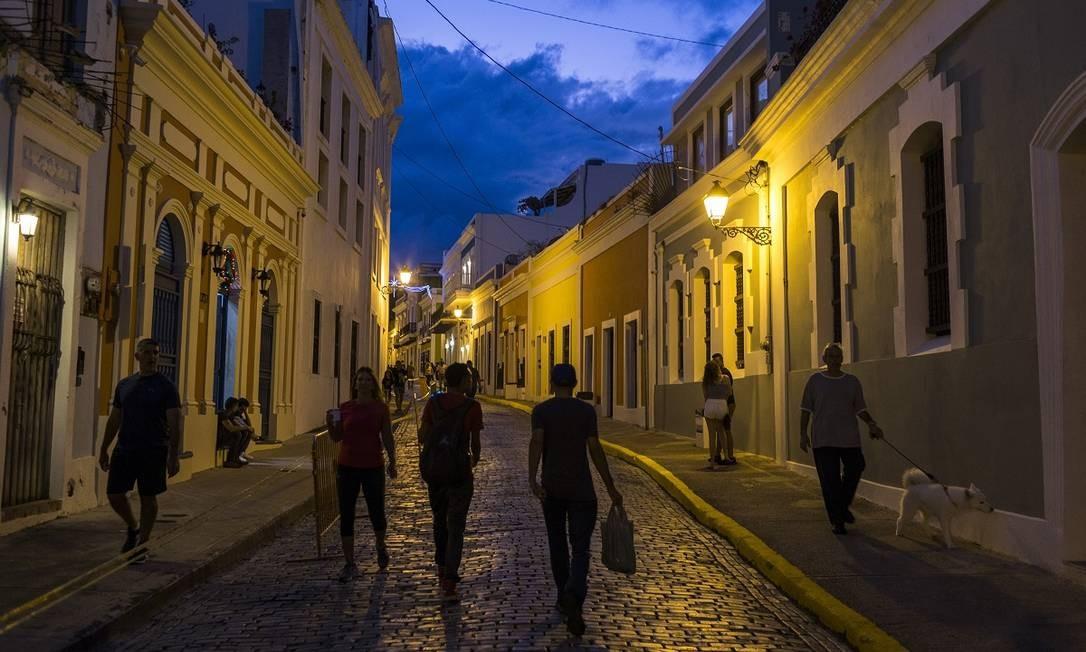 Moradores e visitantes cruzamm uma rua de paralelepípedos no histórico bairro de San Juan Antiguo Foto: Dennis M. Rivera Pichardo / The New York Times