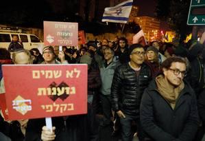 Manifestantes israelenses carregam placas que, em hebraico, dizem