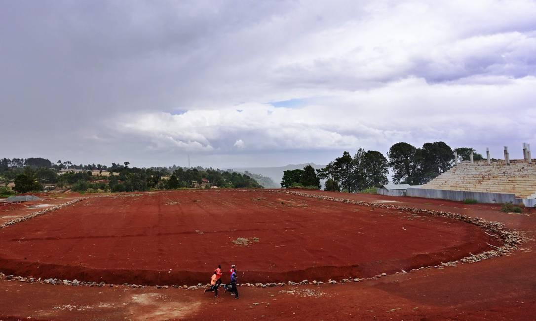 Atletas se aquecem ao longo da pista no histórico Estádio de Kamariny, na cidade de Iten, no Quênia Foto: TONY KARUMBA / AFP