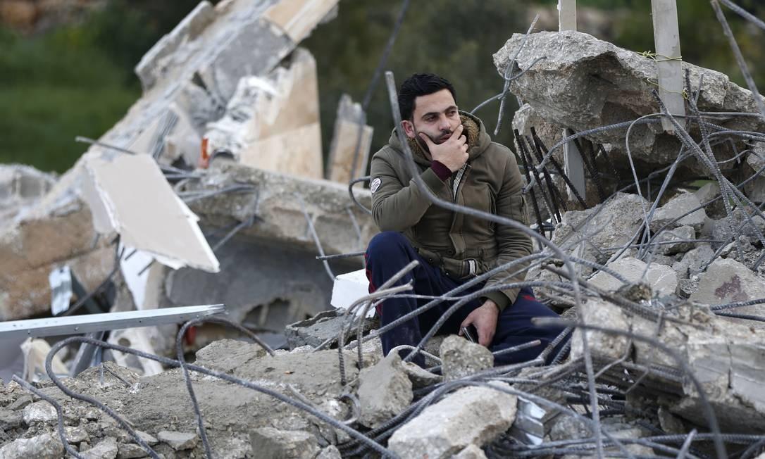 Um homem senta-se nos escombros da casa do palestino Assam Barghouti, acusado por Israel de matar dois soldados na Cisjordânia e ajudar outro ataque que causou a morte de um bebê. A casa foi demolida por forças israelenses na aldeia de Kobar, perto de Ramallah, na Cisjordânia ocupada por Israel Foto: ABBAS MOMANI / AFP