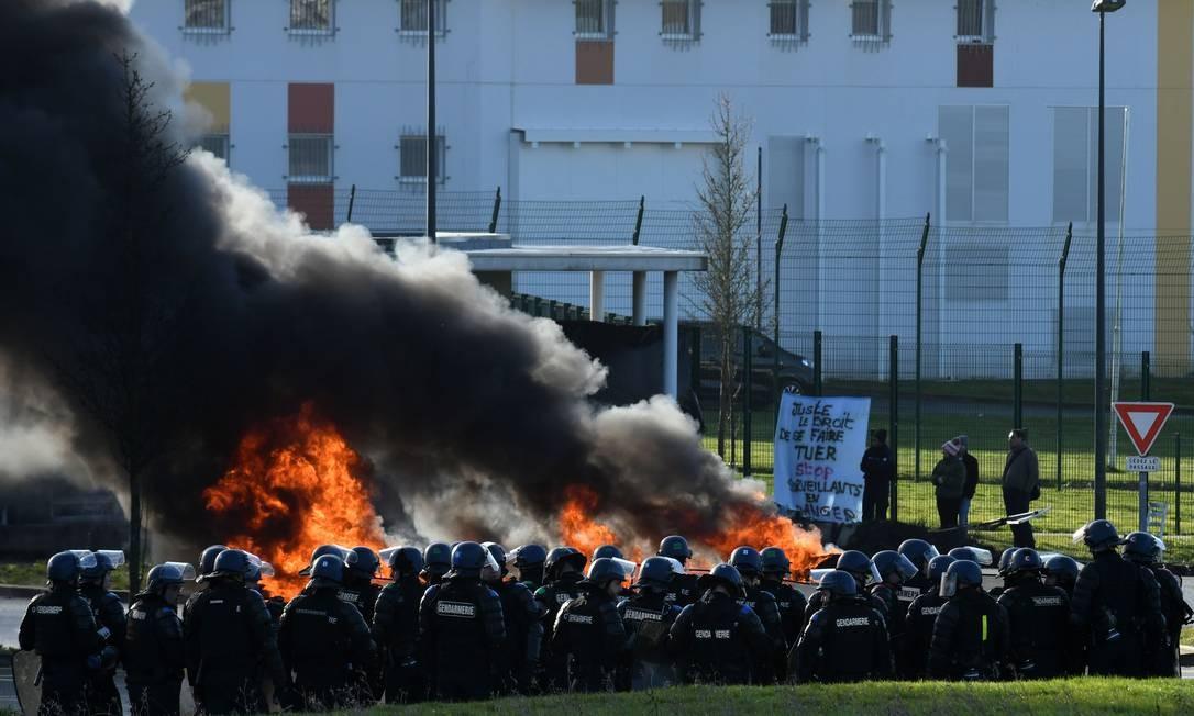 Gendarmes franceses chegam para evacuação enquanto guardas bloqueiam a entrada do centro penitenciário de Alençon, em Condé-sur-Sarthe, no noroeste da França, dois dias depois de um preso ter ferido gravemente dois guardas em um ataque a facadas Foto: JEAN-FRANCOIS MONIER / AFP