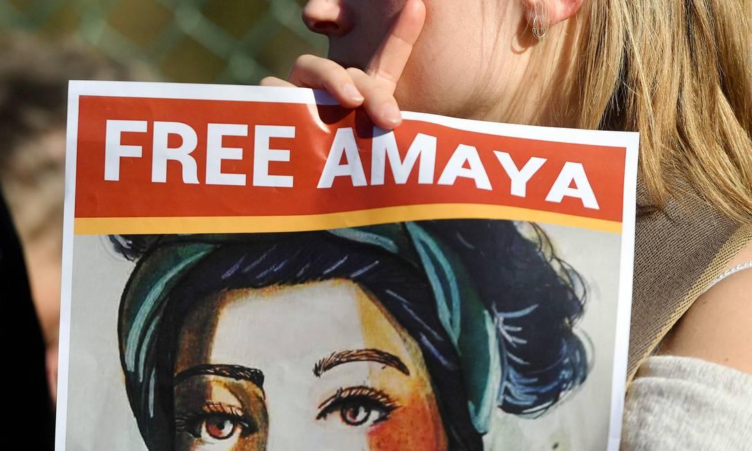 Mulher segura cartaz com rosto de Amaya Coppens, uma das estudantes que iniciou greve de fome em prisão da Nicarágua Foto: EMMANUEL DUNAND / AFP