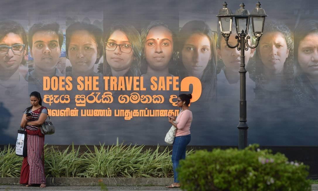 Mulheres passam perto de cartaz que anuncia uma exposição fotográfica em homenagem ao Dia Internacional da Mulher, em Colombo, no Sri Lanka Foto: ISHARA S. KODIKARA / AFP