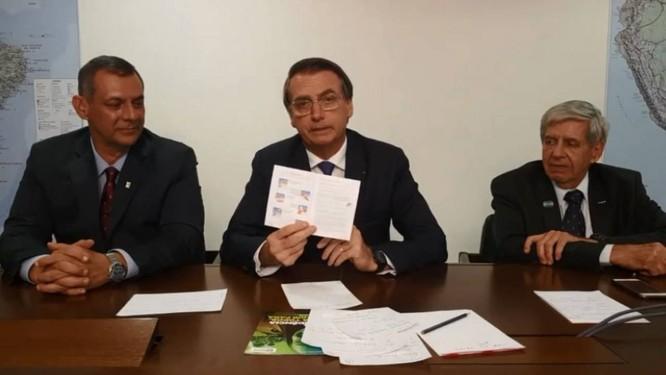 Presidente mostra páginas da cartilha com textos e ilustrações sobre sexo seguro Foto: Reprodução