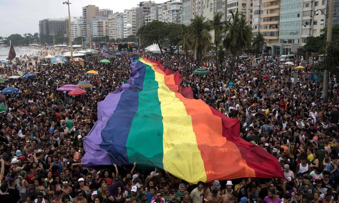 Bandeira arco-íris é levada por multidão em uma parada gay na Praia de Copacabana Foto: LEO CORREA / AFP/19-11-2017