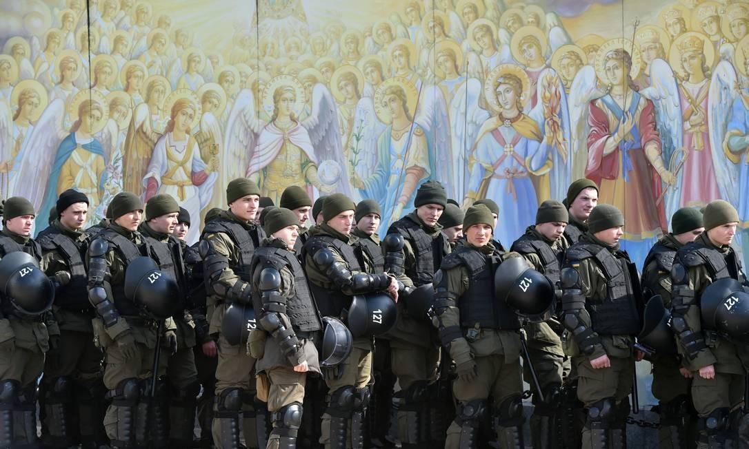 """Em Kiev, capital da Ucrânia, policiais param diante dos afrescos da catedral Mykhaylo Gold Dome enquanto escoltam uma manifestação organizada pela organização pública Insight LGBTQI sob o lema """"Solidariedade e Diversidade"""", por ocasião do Dia Internacional da Mulher Foto: SERGEI SUPINSKY / AFP"""