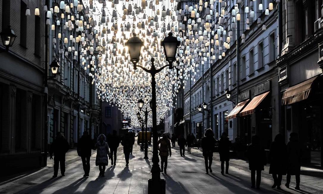 Pessoas, registradas em silhuetas, caminham em uma rua no centro de Moscou na véspera do Dia Internacional da Mulher. A Rússia celebra o dia 8 de março como feriado oficial Foto: MLADEN ANTONOV / AFP