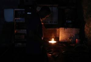 Mecânico usa uma vela para iluminar a oficina em Caracas Foto: IVAN ALVARADO / REUTERS