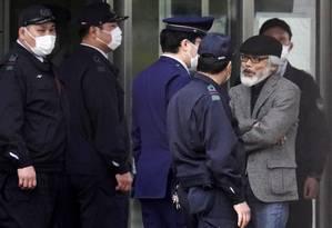 O advogado Takashi Takano (de boina preta) aguarda, junto agentes policiais, a saída de Carlos Ghosn do Centro de Detenção de Tóquio Foto: Bloomberg