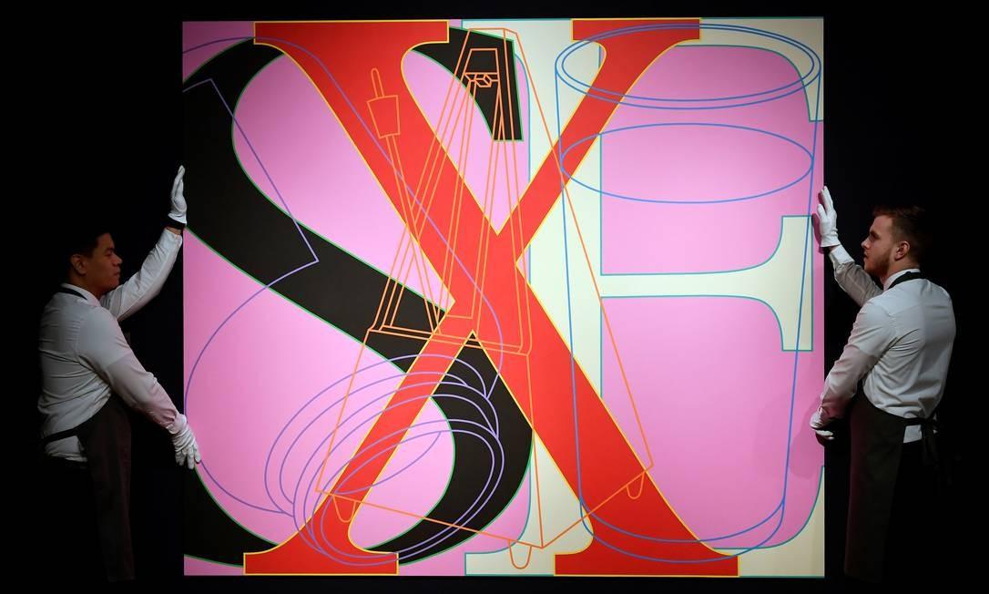 Empregados da Christie's, de Londres, carregam o quadro 'Untitled (SEX)', de Michael Craig-Martin. Obras estão avaliadas entre US$ 522 e US$ 1,9 milhão Foto: TOBY MELVILLE / REUTERS