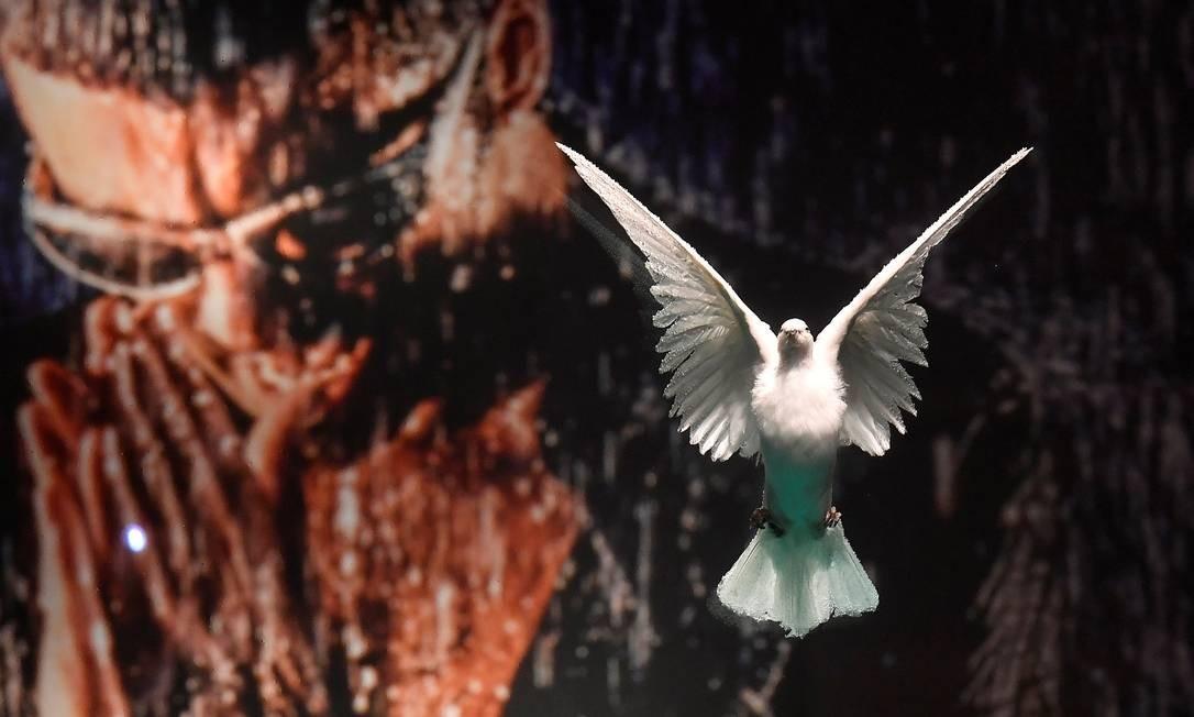 """Um cartaz com a foto de George Michael é visto por trás da obra """"The Incomplete Truth"""", de Damien Hirst - uma pomba envolta em uma solução de formol Foto: TOBY MELVILLE / REUTERS"""