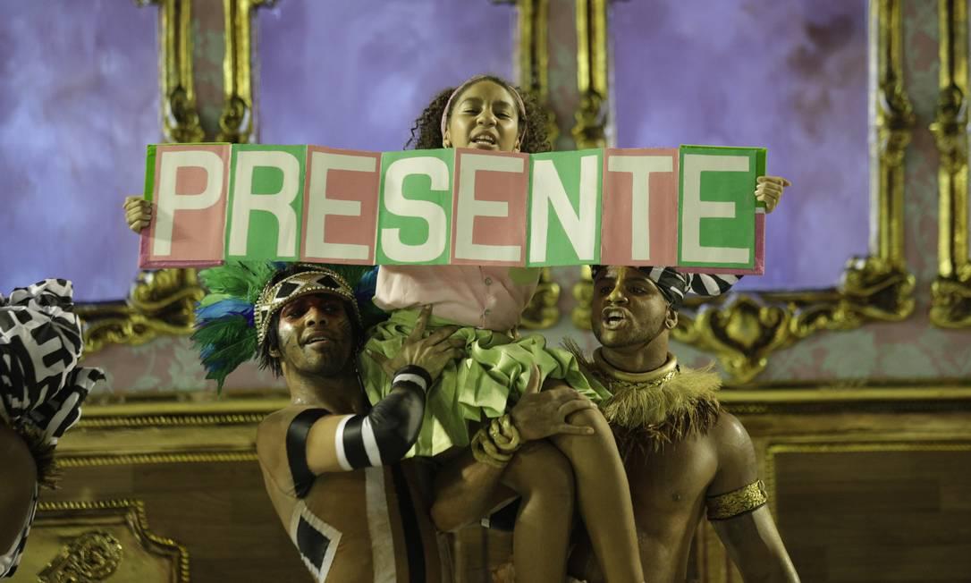 A jovem Cacá Nascimento, destaque da comissão de frente da Mangueira, ergue faixa em homenagem a Marielle: a expressão 'Marielle Presente' ficou conhecida durante a comoção pelo assassinato da parlamentar Foto: GABRIEL MONTEIRO / Agência O Globo