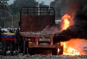 Forças de segurança venezuelanas exibem uma bandeira nacional ao lado de um caminhão que foi incendiado ao tentar entrar no país com ajuda humanitária Foto: RAUL ARBOLEDA / AFP/25-2-2019