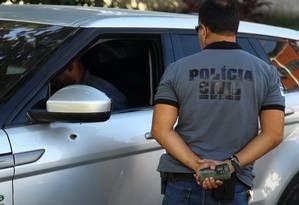 Policiais vistoriam o carro em que a médica foi morta Foto: Agência O Globo