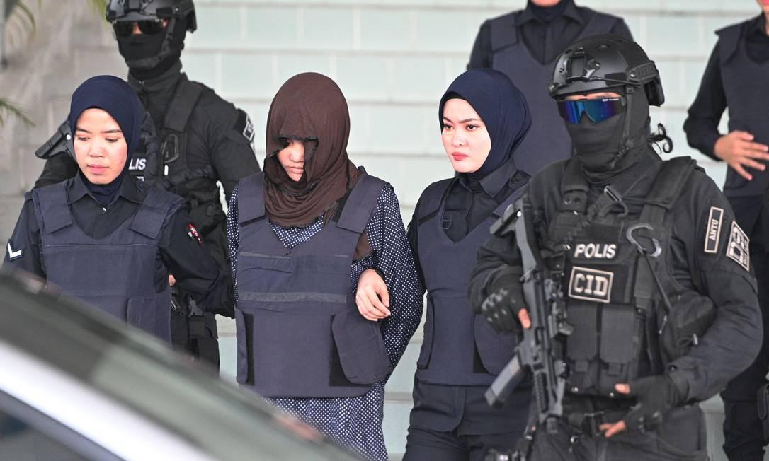 O cidadão vietnamita Doan Thi Huong é escoltado pela polícia malaia depois de uma audiência no Supremo Tribunal de Kuala Lumpur onde acontece seu julgamento por suposto papel no assassinato de Kim Jong nam, o meio-irmão do líder norte-coreano Kim Jong un. A outra acusada de assassinar o meio-irmão do líder norte-coreano deveria ser libertada depois que um promotor retirou uma acusação de assassinato contra ela Foto: MOHD RASFAN / AFP