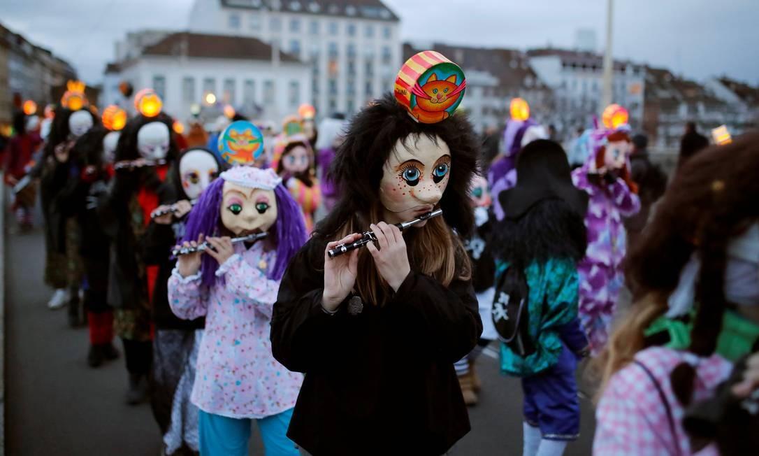 Foliões no Carnaval tocam seus flautins durante o tradicional desfile pelas ruas de Basileia, na Suíça Foto: ARND WIEGMANN / REUTERS