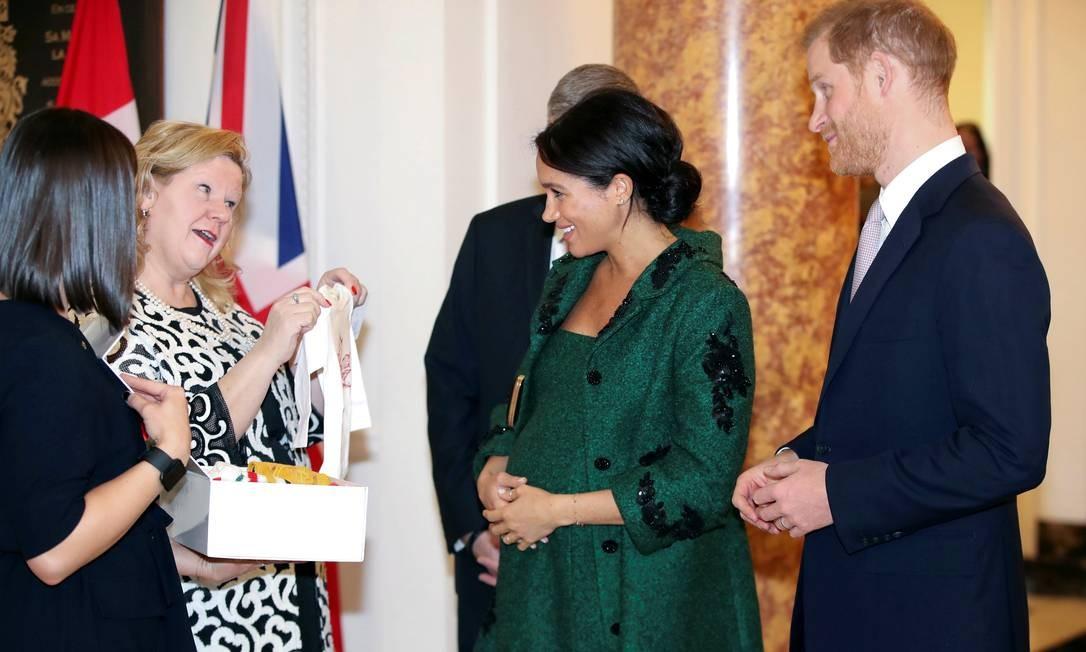 O príncipe da Grã-Bretanha Harry e sua esposa Meghan ganham um mimo da comissária canadense para o Reino Unido Janice Charette durante um evento com jovens no Canadá House em Londres Foto: POOL / REUTERS