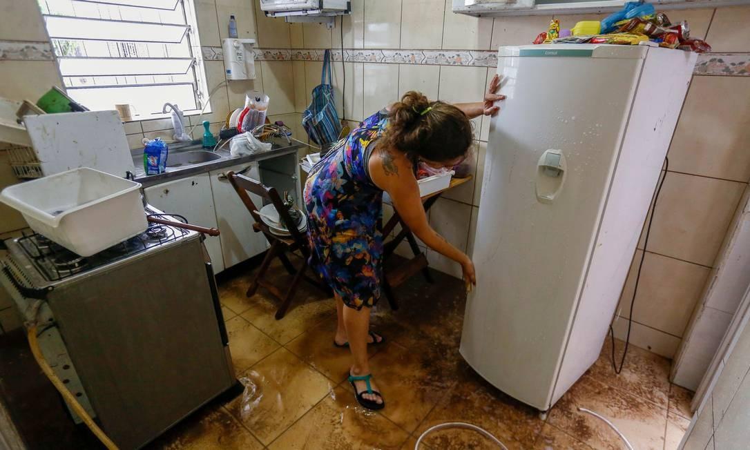 Uma mulher tenta limpar a casa que foi invadida pela lama Foto: MIGUEL SCHINCARIOL / AFP