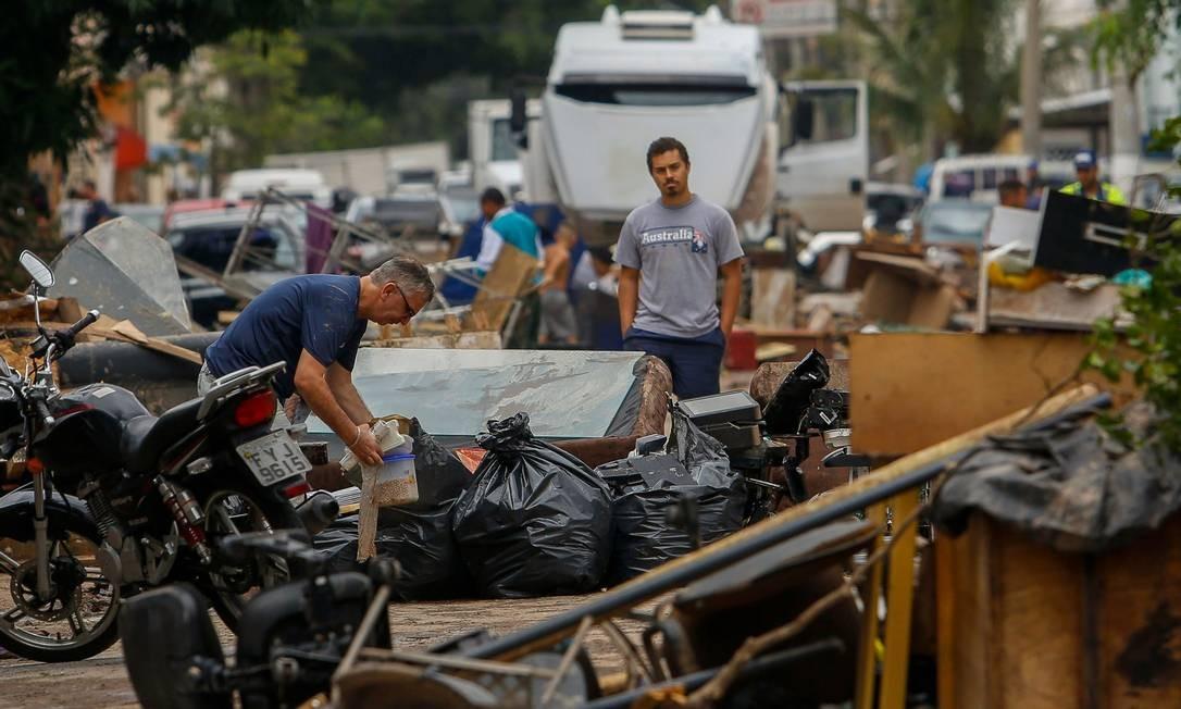 Um homem tenta salvar seus pertences danificados pela chuva em São Paulo. 11.03.2019. Foto: Foto: Miguel SCHINCARIOL / AFP