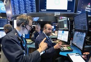 Traders em Wall Street: informar-se antes de investir é essencial. Foto: BRENDAN MCDERMID / REUTERS