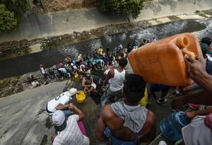 Venezuelanos coletam água do rio Guaire em Caracas durante mega apagão que atinge diversas partes do país Foto: JUAN BARRETO / AFP/11-03-2018