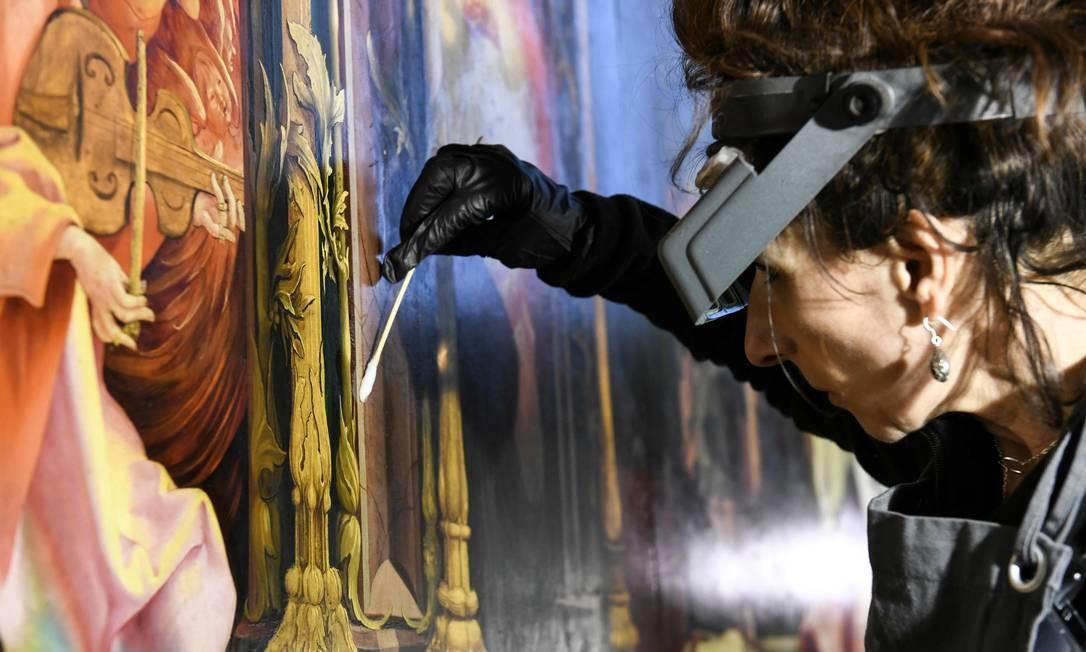"""Uma mulher trabalha na restauração da pintura """"O concerto dos anjos"""", obra de Matthias Grunewald entre os anos de 1512 / 1516 Foto: SEBASTIEN BOZON / AFP"""