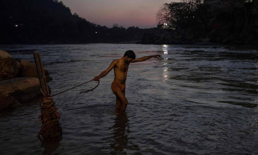 Devoto hindu indiano segura uma corda enquanto se banha no rio Ganges ao pôr do sol, em Rishikesh, no estado indiano de Uttarakhand Foto: XAVIER GALIANA / AFP