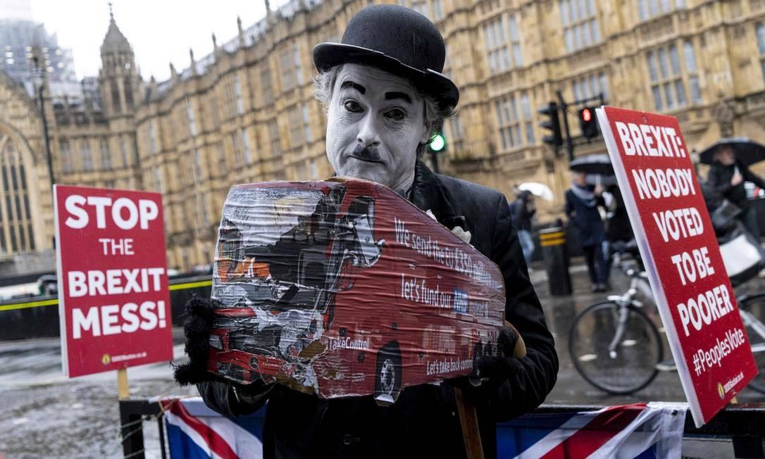 Ativista anti-Brexit segura cartaz durante manifestação em Londres; o Parlamento britânico rejeitou nesta terça (12) pela segunda vez o acordo que define os termos da saída do Reino Unido da União Europeia (UE), aumentando a incerteza sobre a permanência da conservadora Theresa May no cargo de primeira-ministra Foto: NIKLAS HALLE'N / AFP