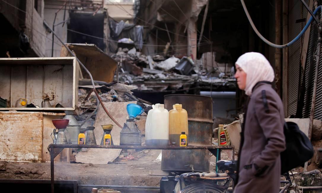 Uma mulher passa pelo combustível colocado à venda em Ein Terma, um distrito do leste de Ghouta, na Síria, Foto: OMAR SANADIKI / REUTERS