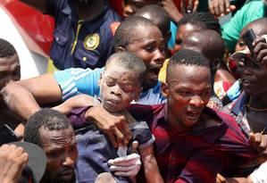 Homens carregam criança salva de escombros após desabamento de escola em Lagos, na Nigéria Foto: TEMILADE ADELAJA / REUTERS
