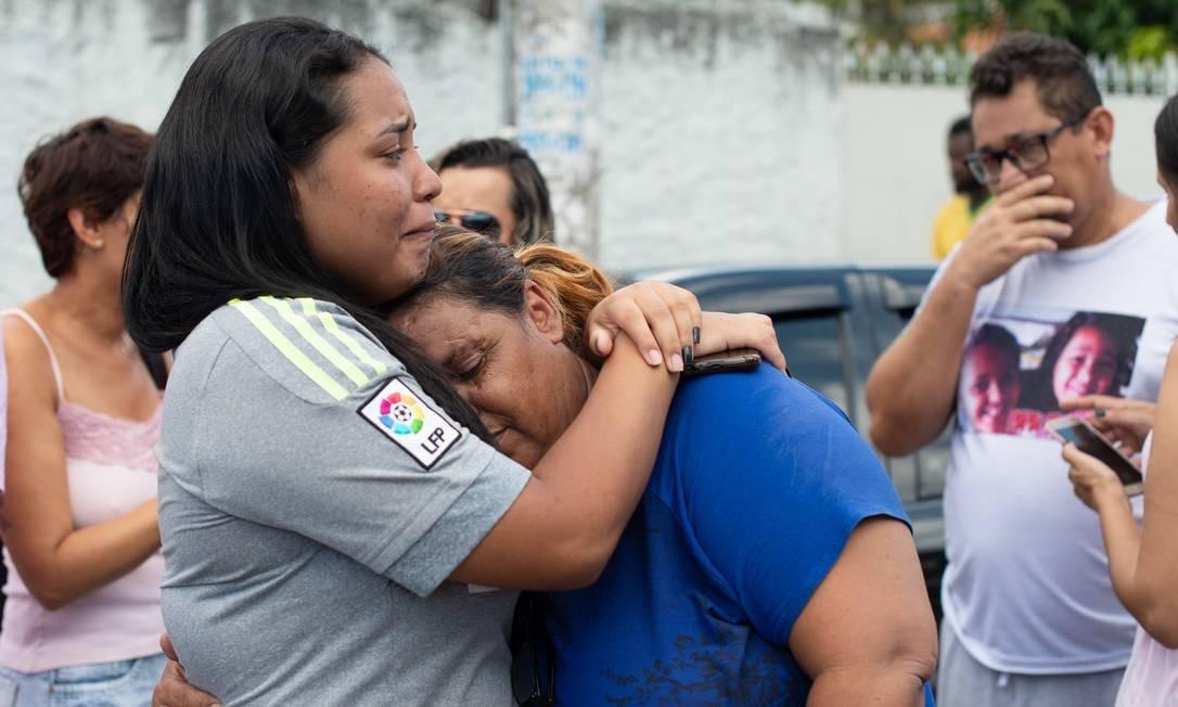 Familiares e amigos de estudantes se consolam em meio ao desespero em frente à Escola Raul Brasil, após atentado Foto: Julien Pereira/Fotoarena / Agência O Globo