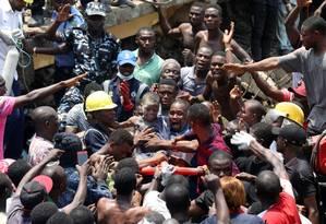 Homens carregam criança resgatada do desabamento de um prédio em Lagos, na Nigéria Foto: TEMILADE ADELAJA / REUTERS