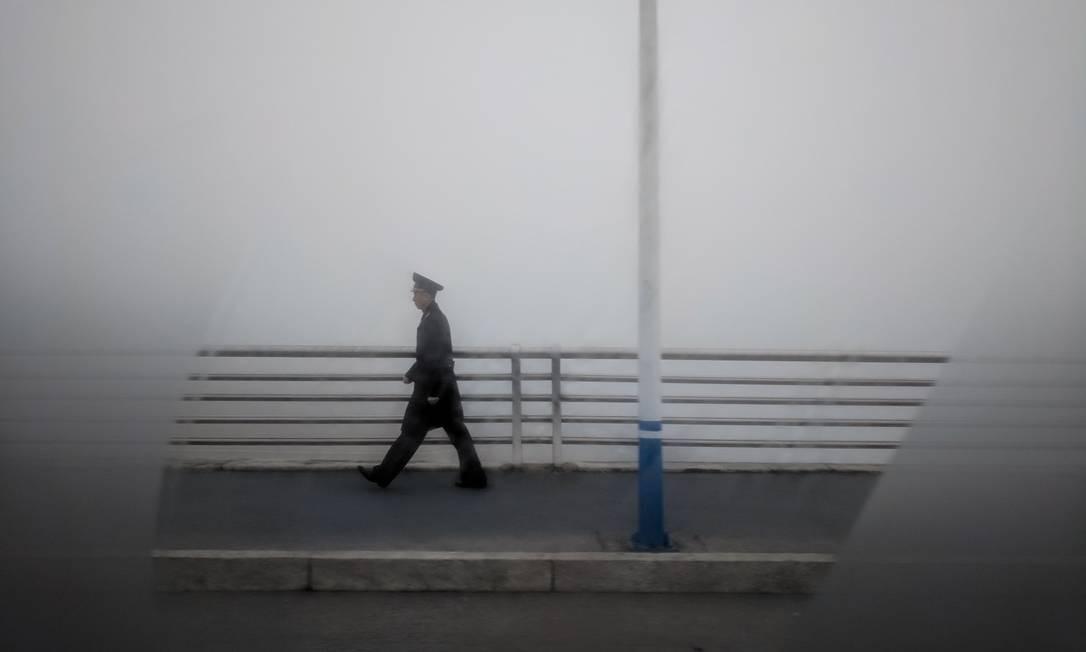 Funcionário do aeroporto atravessa uma ponte perto do aeroporto internacional de Sunan, nos arredores de Pyongyang, na Coreia do Norte Foto: ED JONES / AFP