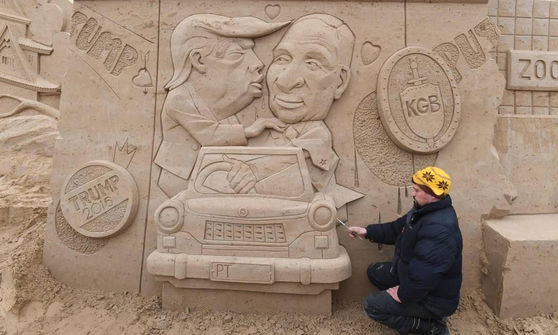 """O escultor polonês Wodek Bludik trabalha na escultura em areia """"Muro de Berlim"""", com uma interpretação do grafite na galeria Eastside de Berlim, chamada """"Brother Kiss"""", apresentando o presidente dos EUA, Donald Trump, e seu colega russo, Vladimir Putin Foto: STEFAN SAUER / AFP"""