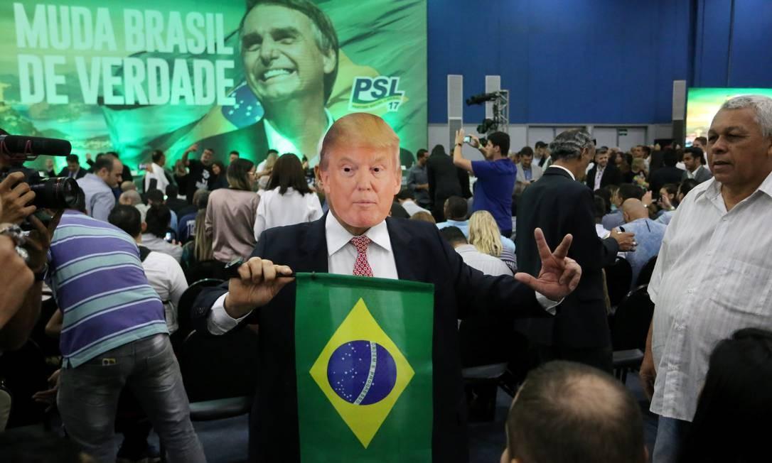 Partidário de Jair Bolsonaro usando máscara com o rosto de Trump segura bandeira do Brasil no lançamento da campanha do então candidato à Presidência: agenda externa focada em 'reforçar a relação com os países que podem contribuir para o desenvolvimento, a prosperidade, o bem-estar e a segurança' do Brasil Foto: Guilherme Pinto/22-07-2018