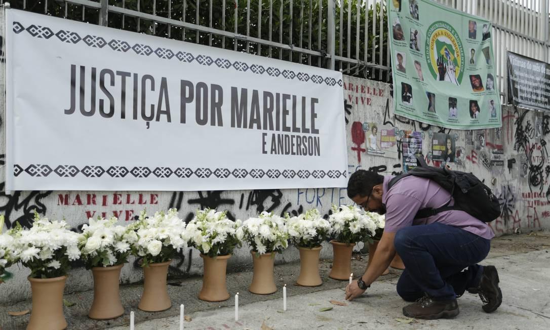 Homem acende vela no lugar onde Marielle e o motorista Anderson Gomes foram executados Foto: Gabriel de Paiva / Agência O Globo