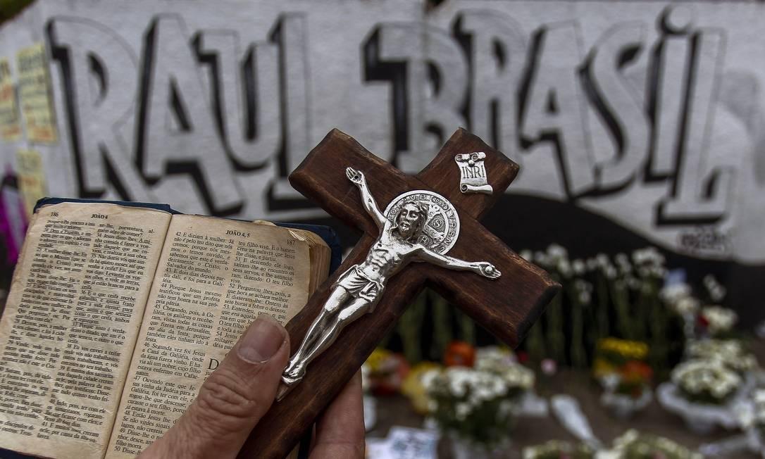 Um homem segura uma Bíblia e uma cruz do lado de fora da escola pública Raul Brasil, um dia depois de um ataque no qual dez pessoas morreram – incluindo os dois atiradores – e outras 15 ficaram feridas em Suzano, região metropolitana de São Paulo Foto: MIGUEL SCHINCARIOL / AFP