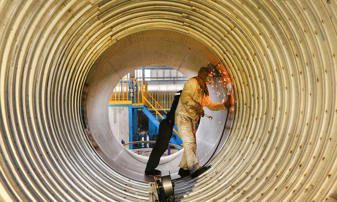 Um trabalhador solda um tanque de gás natural liquefeito (GNL) em uma fábrica em Nantong, no Leste da província de Jiangsu. A produção industrial da China desacelerou durante os dois primeiros meses do ano, segundo dados oficiais Foto: STR / AFP
