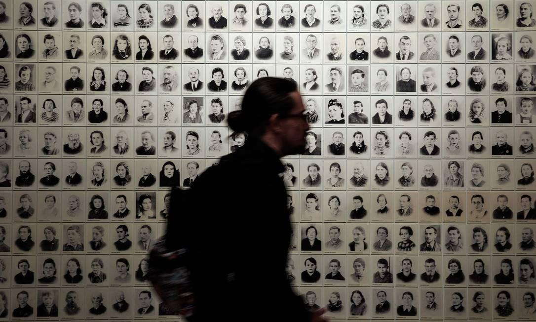 Um visitante caminha em frente a um mosaico de 600 fotografias de judeus de Bedzin, cidade da Polônia, durante a abertura oficial do Centro de Holocausto e Genocídio em Joanesburgo, África do Sul Foto: GIANLUIGI GUERCIA / AFP