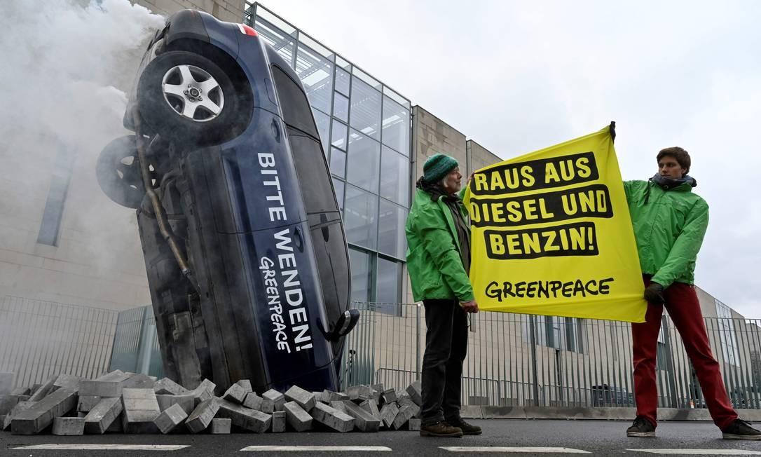 """Ativistas do Greenpeace seguram uma faixa com a frase """"De diesel e benzina"""" diante de um carro tombado durante uma ação de protesto em frente à chancelaria, onde acontece uma reunião sobre proteção climática no setor de transportes, em Berlim, na Alemanha Foto: JOHN MACDOUGALL / AFP"""