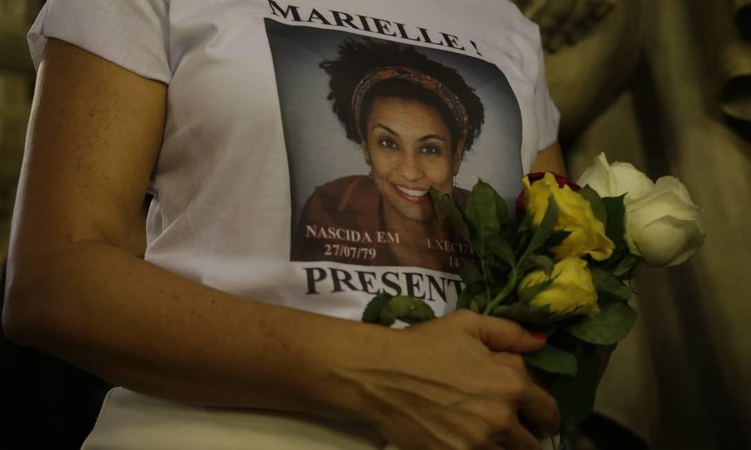 Mulher segura flores na missa em lembrança da data de 1 ano da morte de Marielle Franco, na Candelária Foto: Gabriel Paiva / Gabriel Paiva