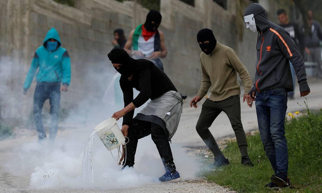 Um manifestante palestino joga água em uma bomba de gás lacrimogêneo durante confrontos com forças israelenses, perto de Ramallah, na Cisjordânia, ocupada por Israel Foto: MOHAMAD TOROKMAN / REUTERS