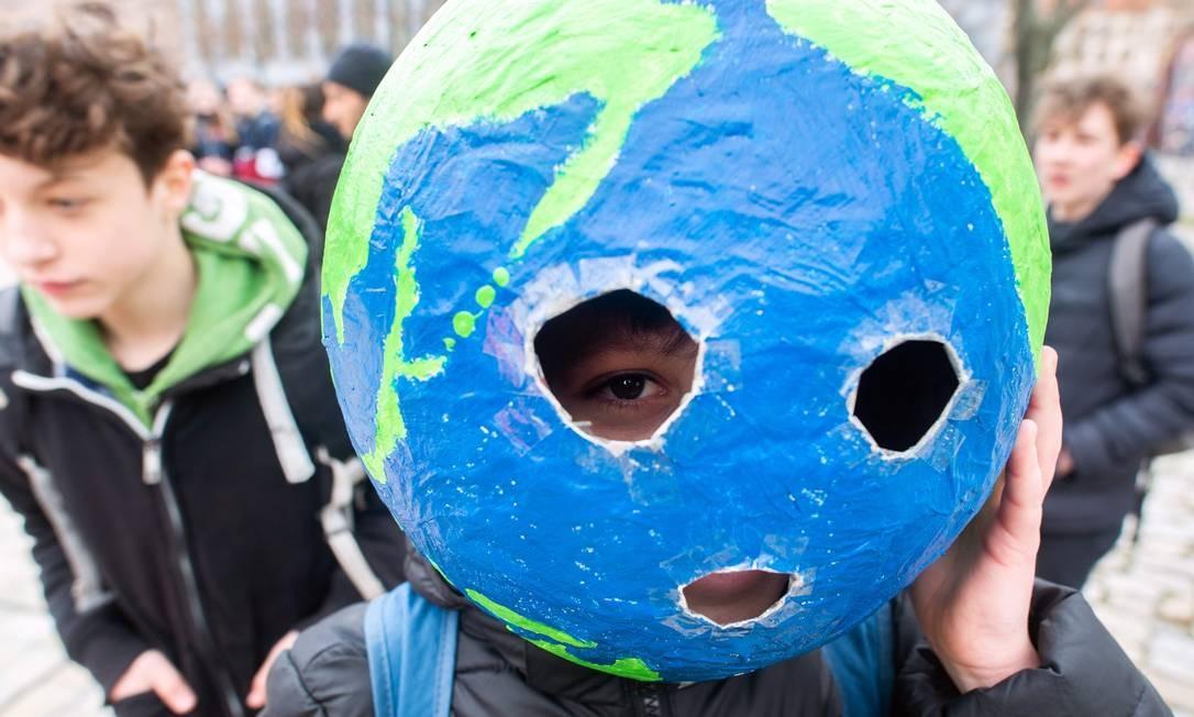 """Em Berlim, um jovem usa uma máscara que imita o globo terrestre durante o movimento """"sextas-feiras para o futuro"""", em um dia mundial de protestos estudantis com o objetivo de incitar líderes mundiais a agir em relação à mudança climática Foto: KLAUS-DIETMAR GABBERT / AFP"""
