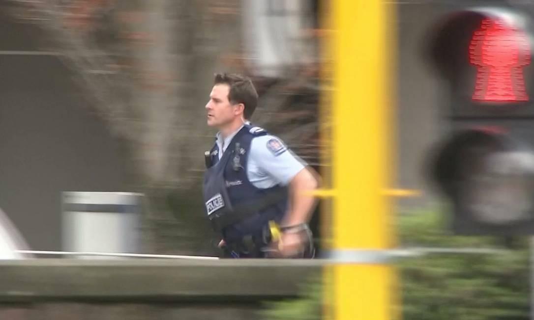 Imagem de vídeo mostra momento em que um policial corre em direção a uma das mesquitas atacadas no centro de Christchurch, Nova Zelândia. Ao menos 49 pessoas morreram; outras 48 ficaram feridas, sendo 20 em estado grave Foto: REUTERS TV / REUTERS