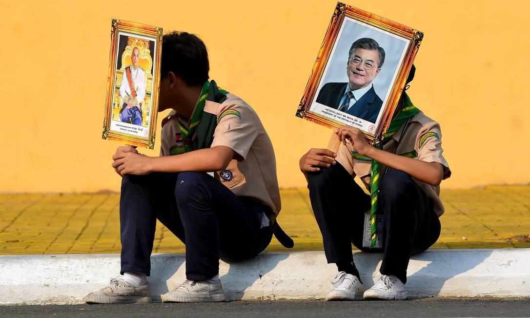 Escoteiros seguram retratos do rei cambojano, Norodom Sihamoni, e do presidente da Coréia do Sul, Moon Jae-in, enquanto esperam no Palácio Real em Phnom Penh. O líder sul-coreano está em sua terceira etapa da turnê pelo Sudeste Asiático em Brunei, Malásia e Camboja Foto: TANG CHHIN SOTHY / AFP